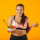 Portrait of a cheerful overweight fitness woman wearing sports clothing standing isolated over yellow background, holding bowl with salad and a burger